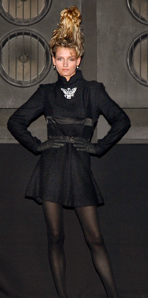 The catwalk model Stephanie in a classic black exquisite wool dress decorated with embroidery symbol on the chest from the new trend collection autumn / winter 2008 - 2009 by German fashion designer Torsten Amft to Fashion Week Berlin - photographer M. Wittig